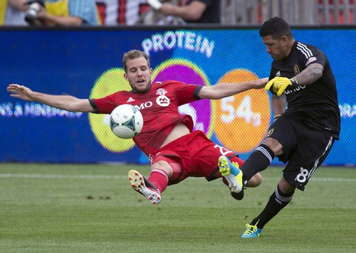 Toronto FC forward Jeremy Brockie, left, dives in with a sliding challenge as Real Salt Lake goalkeeper Eduardo Fernandez clears ball during the first half of an MLS soccer game in Toronto on Saturday June 29, 2013. (AP Photo/The Canadian Press, Frank Gunn)