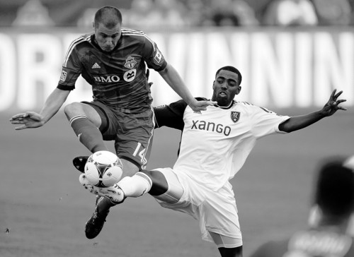 Toronto FC forward Danny Koevermans, left, and Real Salt Lake defender Aaron Maund battle for the ball during the first half of an MLS soccer game in Toronto on Saturday June 29, 2013. (AP Photo/The Canadian Press, Frank Gunn)
