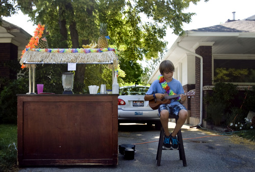 Kim Raff  |  The Salt Lake Tribune Ben Summa strums a ukulele while waiting for thirsty patrons at his Smoothie Shack outside his home on 600 East in Salt Lake City on June 29, 2013. Utah is in the middle of a record-breaking heat wave with no cool weather relief in sight.