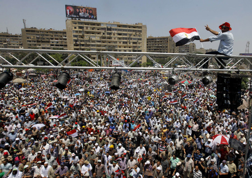 Supporters of Egypt's Islamist President Mohammed Morsi wave his posters and national flags as they fill a public square outside of the Rabia el-Adawiya Mosque in Cairo, not far from the presidential palace, during a rally in Cairo, Saturday, June 29, 2013.  Thousands of supporters and opponents of Egypt's embattled Islamist president are holding rival sit-ins on the eve of what are expected to be massive opposition-led protests aimed at forcing Mohammed Morsi's ouster. The demonstrations early Saturday follow days of deadly clashes in a string of cities across the country that left at least seven people dead, including an American, and hundreds injured. (AP Photo/Amr Nabil)