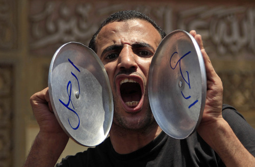 "An opponent of Egypt's Islamist President Mohammed Morsi chants slogans as he holds pot covers with Arabic that reads, ""leave,"" during a protest outside the presidential palace, in Cairo, Egypt, Sunday, June 30, 2013. Thousands of Egyptians demanding the ouster of Morsi are gathering at Cairo's central Tahrir Square and the presidential palace at the start of a day of massive, nationwide protests many fear could turn deadly. (AP Photo/Khalil Hamra)"