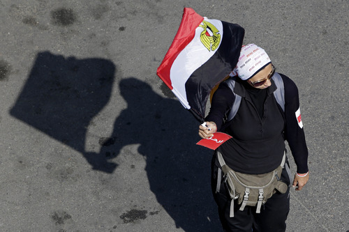A woman holds an Egyptian national flag during a protest calling for the ouster of Islamist President Mohammed Morsi outside the presidential palace in Cairo, Egypt, Sunday, June 30, 2013. Thousands of Egyptians demanding the ouster of Morsi are gathering at Cairo's central Tahrir Square and the presidential palace at the start of a day of massive, nationwide protests many fear could turn deadly. (AP Photo/Hassan Ammar)