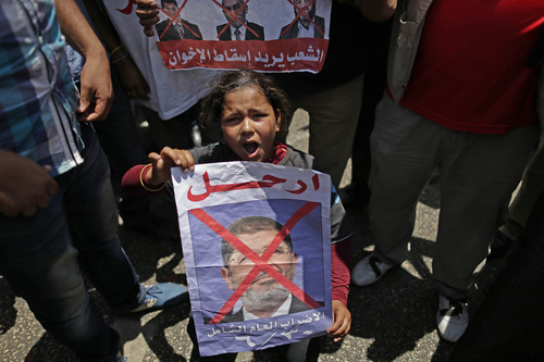 """An Egyptian girl holds a poster with Arabic that reads, """"Heave, Huge year strike,"""" as she chants slogans during a protest against Egypt's Islamist President Mohammed Morsi outside the presidential palace, in Cairo, Egypt, Sunday, June 30, 2013. Organizers of a mass protest against Morsi claimed Saturday that more than 22 million people have signed their petition demanding the Islamist leader step down, asserting that the tally was a reflection of how much the public has turned against his rule. (AP Photo/Hassan Ammar)"""