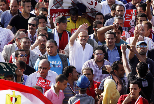 Egyptian reform leader Mohamed ElBaradei, center, waves from the crowd during a protest calling for the ouster of President Mohammed Morsi in Cairo, Sunday, June 30, 2013. Hundreds of thousands of opponents of Egypt's Islamist president poured out onto the streets in Cairo and across much of the nation Sunday, launching an all-out push to force Mohammed Morsi from office on the one-year anniversary of his inauguration. Fears of violence were high, with Morsi's Islamist supporters vowing to defend him. (AP Photo/Mostafa Elshemy)