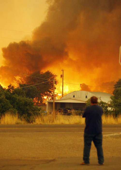 Dean Smith watches as the Yarnell Hill Fire encroaches on his home in Glenn Ilah on Sunday, June 30, 2013 near Yarnell, Ariz. The fire started Friday and picked up momentum as the area experienced high temperatures, low humidity and windy conditions. It has forced the evacuation of residents in the Peeples Valley area and in the town of Yarnell. (AP Photo/The Arizona Republic, David Kadlubowski)