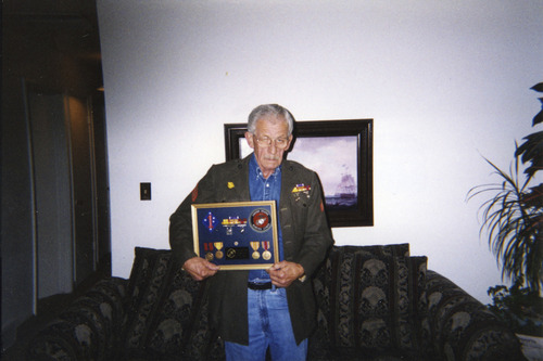 Courtesy photo Walt Youse holds a shadow box with the Purple Heart ribbon and other medals and awards he earned in the Pacific Theater in World War II. Youse died two years ago, before the Department of Veterans Affairs could decide whether he deserved disability pay for his war injuries.