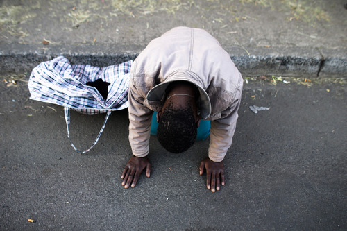 A man kneels on the street to pray for former South African President Nelson Mandela outside the side entrance of the Mediclinic Heart Hospital where Nelson Mandela is being treated in Pretoria, South Africa, Monday, July 1, 2013. Former president Nelson Mandela remained in a critical condition on Monday. (AP Photo/Markus Schreiber)