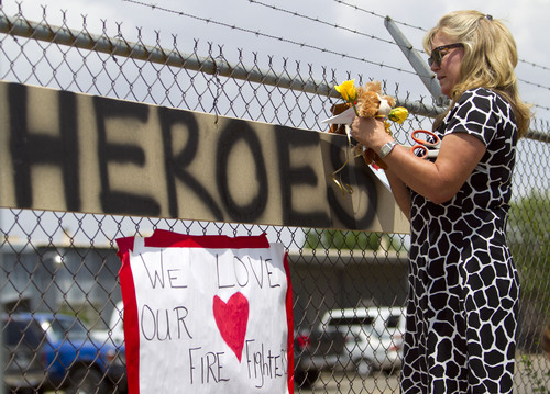 Maggie Greenwood adds flowers to a makeshift memorial at the fire station Monday, July 1, 2013, in Prescott, Ariz., where an elite team of firefighters was based. Nineteen of the 20 members of the team were killed Sunday when a wildfire suddenly swept toward them in Yarnell, Ariz. (AP Photo/The Arizona Republic, David Wallace)