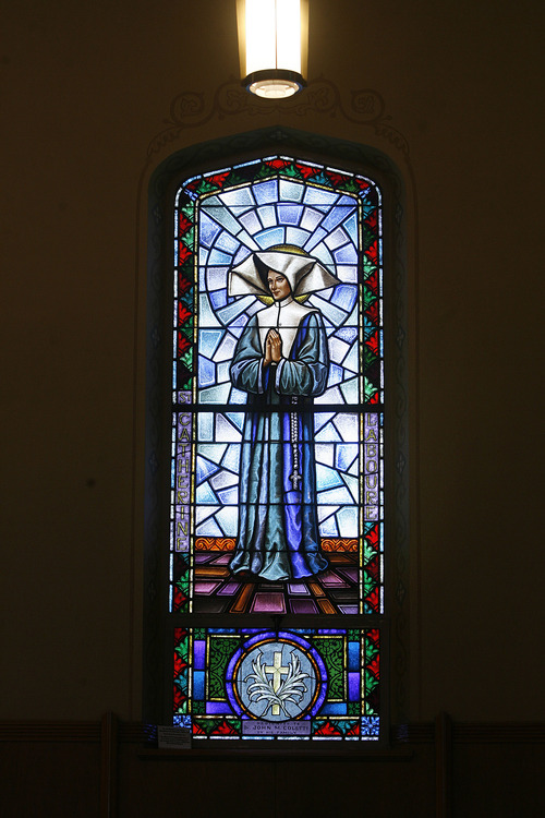 Scott Sommerdorf   |  The Salt Lake Tribune Stained glass of St. Catherine Laboure, a Frenchwoman who had mystical visions. The window is inside Our Lady of Lourdes Catholic Church.  The church is celebrating its 100th anniversary. Sunday, June 23, 2013.