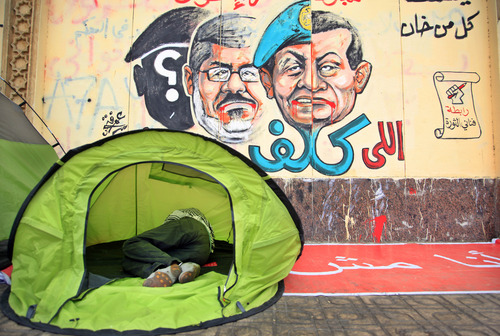 """An opponent of Egypt's Islamist President Mohammed Morsi sleeps in a tent next to a wall graffiti with Arabic writing reads who assigned you did not die""""  as he and others protest outside the presidential palace in Cairo, Egypt, Tuesday, July 2, 2013. Egypt was on edge Tuesday following a """"last-chance"""" ultimatum the military issued to Mohammed Morsi, giving the president and the opposition 48 hours to resolve the crisis in the country or have the army step in with its own plan. (AP Photo/Khalil Hamra)"""