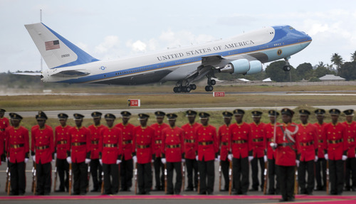 Air Force One takes off as a Tanzanian honor guard stands to attention, as U.S. President Barack Obama finishes the final leg of his weeklong visit to Africa, at the Julius Nyerere airport in Dar es Salaam, Tanzania Tuesday, July 2, 2013. President Barack Obama on Monday courted African business leaders and announced new trade initiatives to open up East Africa's markets to American businesses, as he sought to counter the rise of Chinese economic influence in the growing continent. (AP Photo/Ben Curtis)