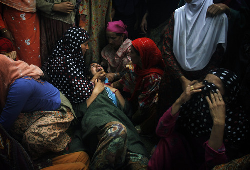 Relatives cry near the body of Shahnawaz Mir, a suspected militant commander of Hizb-ul Mujahedeen, Kashmir's biggest rebel group,  during his funeral at Tral, some 40 kilometers (25 miles) south of Srinagar, India, Tuesday, July 2, 2013. Three Hizb-ul Mujahedeen (HM) militants and a policeman were killed after a fierce gunfight broke out between Indian security forces and militants in this south Kashmir district on Monday. (AP Photo/Mukhtar Khan)