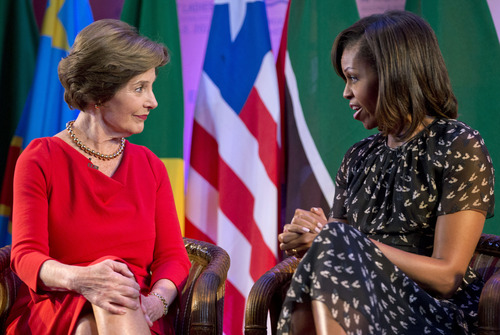 """U.S. first lady Michelle Obama, left, and former U.S. first lady Laura Bush look to each other as they participate in the African First Ladies Summit: """"Investing in Women: Strengthening Africa,"""" hosted by the George W. Bush Institute, Tuesday, July 2, 2013, in Dar es Salaam, Tanzania. (AP Photo/Carolyn Kaster)"""