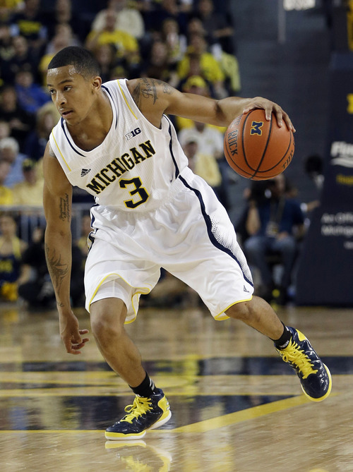 Michigan guard Trey Burke (3) dribbles upcourt during the second half of an NCAA college basketball game against Iowa at Crisler Arena in Ann Arbor, Mich., Sunday, Jan. 6, 2013. (AP Photo/Carlos Osorio)
