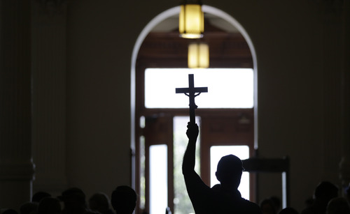 An anti-abortion supporter carries a cross as he enters the Texas capitol, Monday, July 1, 2013, in Austin, Texas. The Texas Senate has convened for a new 30-day special session to take up a contentious abortion restrictions bill and other issues. (AP Photo/Eric Gay)