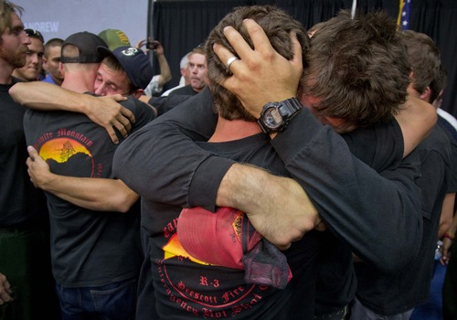 Prescott and other area department firefighters embrace during a memorial service, Monday, July 1, 2013 in Prescott, Ariz. for the 19 Granite Mountain Hotshot Crew firefighters who were killed Sunday, when an out-of-control blaze overtook the elite group. (AP Photo/Julie Jacobson)