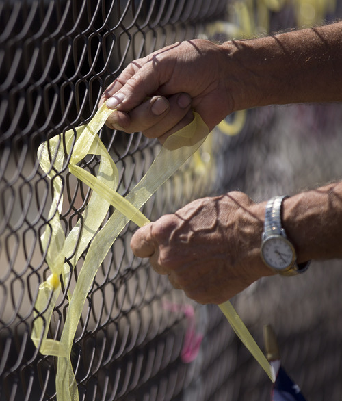 Dave Anderson ties a yellow ribbon into the shape of a heart on the fence outside the Granite Mountain Interagency Hotshot Crew fire station, Tuesday, July 2, 2013 in Prescott, Ariz. Nineteen members of the Granite Mountain Hotshots, based in Prescott, were killed Sunday when a windblown wildfire overcame them north of Phoenix. It was the deadliest single day for U.S. firefighters since 9/11. Fourteen of the victims were in their 20s. (AP Photo/Julie Jacobson)