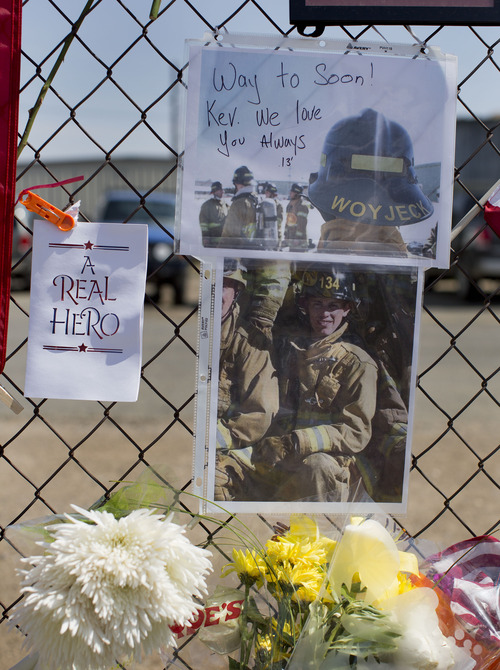 A photo of Hotshot firefighter Kevin Woyjeck hangs on a fence outside the Granite Mountain Interagency Hotshot Crew fire station, Tuesday, July 2, 2013 in Prescott, Ariz. Woyjeck was one of 19 members of the Granite Mountain Hotshots, based in Prescott, who were killed Sunday when a windblown wildfire overcame them north of Phoenix. It was the deadliest single day for U.S. firefighters since 9/11. Fourteen of the victims were in their 20s.   (AP Photo/Julie Jacobson)