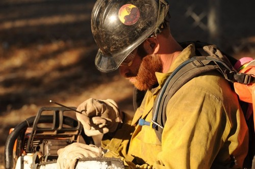 In this June 2013 photo provided by the Prescott Fire Department via the Prescott Daily Courier, Dustin Deford, a member of the Prescott Fire Department Granite Mountain Hotshots, sharpens his chainsaw while working a fire near Prescott, Ariz. DeFord, 24, who grew up in Ekalaka, Mont., died Sunday, June 30, 2013 with 18 other firefighters when they were overtaken by an out-of-control blaze. (AP Photo/Prescott Fire Department via the Prescott Daily Courier)