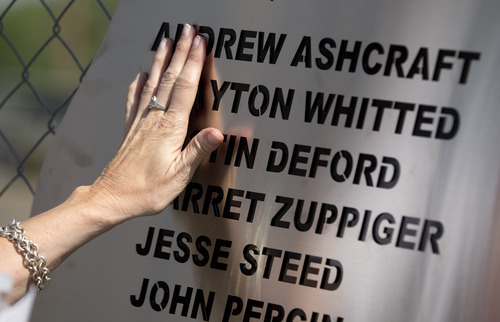 Linda Lambert places her hand across a plaque hanging on the fence outside the Granite Mountain Interagency Hotshot Crew fire station, Tuesday, July 2, 2013 in Prescott, Ariz.  The plaque holds the names of the 19 firefighters killed Sunday, by an out-of-control blaze near Yarnell, Ariz.  Lambert is the aunt of firefighter Andrew Ashcraft. (AP Photo/Julie Jacobson)