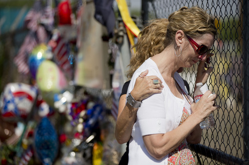 Linda Lambert is comforted by her friend Margo Williams as she visits the memorial outside the Granite Mountain Interagency Hotshot Crew fire station, Tuesday, July 2, 2013 in Prescott, Ariz. Lambert is the aunt of Andrew Ashcraft, one of the 19 firefighters killed Sunday, by an out-of-control blaze near Yarnell, Ariz. (AP Photo/Julie Jacobson)