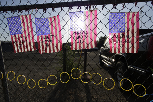 Flags with the names of the fallen firefighters hang at a makeshift memorial outside the Granite Mountain Interagency Hotshot Crew fire station, Tuesday, July 2, 2013  in Prescott, Ariz. The elite crew of firefighters were overtaken by the out-of-control blaze battling a wildfire near Yarnell, Ariz., Sunday as they tried to protect themselves from the flames under fire-resistant shields. (AP Photo/Chris Carlson)