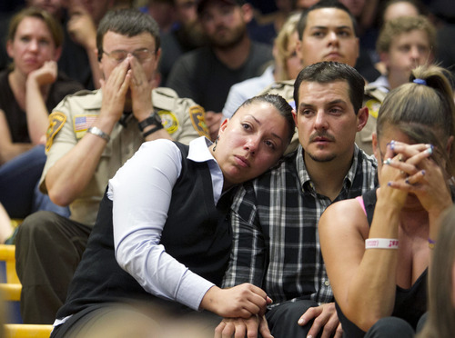Gina Martinez, center, and Chase Madrid, center right, comfort each other during a memorial service for 19 firefighters of the Granite Mountain Hotshot Crew that were killed battling a wildfire,  Monday, July 1, 2013 in Prescott, Ariz.  Madrid is a former Granite Mountain Hotshot and knew many of the firefighters who were killed. (AP Photo/The Arizona Republic, David Wallace)