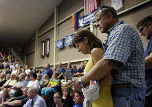 Marsha McKee and Stanley Nesheim react during a memorial service for 19 firefighters of the Granite Mountain Hotshot Crew,  Monday, July 1, 2013 in Prescott, Ariz. McKee is the mother of one of the Hotshots who were killed by an out-of-control blaze near Yarnell, Ariz. on Sunday. (AP Photo/Chris Carlson)