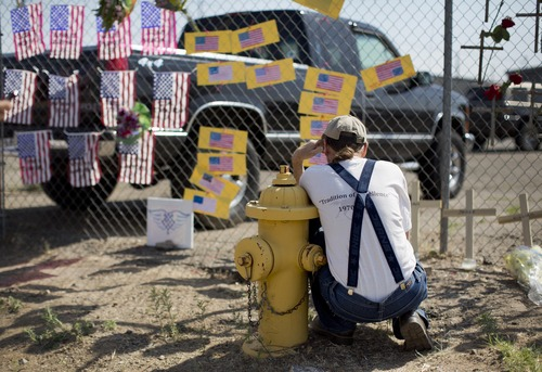 Stephen Grady reads various notes left at the Granite Mountain Interagency Hotshot Crew fire station, Tuesday, July 2, 2013 in Prescott, Ariz. Nineteen members of the Granite Mountain Hotshots, based in Prescott, were killed Sunday when a windblown wildfire overcame them north of Phoenix. It was the deadliest single day for U.S. firefighters since 9/11. Fourteen of the victims were in their 20s. (AP Photo/Julie Jacobson)