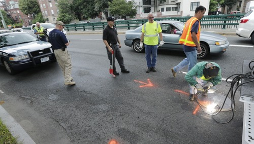 A manhole cover on Storrow Drive, adjacent to Boston's Esplanade, is welded shut after being checked for explosives by state and military officials, Tuesday, July 2, 2013, in Boston.  Law enforcement has increased their security effort for the Independence Day celebration, the first major public gathering since the Boston Marathon bombings. (AP Photo/Charles Krupa)
