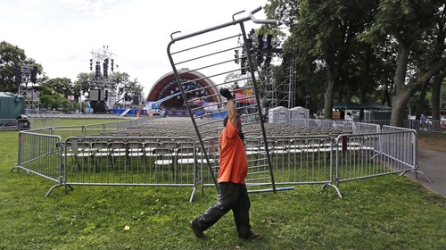 A worker carries a crowd control fence, while setting up a security perimeter on the Esplanade, near the site of the Fourth of July fireworks and concert, Tuesday, July 2, 2013, in Boston.  Law enforcement has increased their security effort for the Independence Day celebration, the first major public gathering since the Boston Marathon bombings. (AP Photo/Charles Krupa)