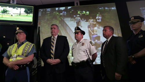 As law enforcement officials stand during a news conference, a family is seen crossing a footbridge on a surveillance monitor from the Charles River Esplanade, at the Unified Command Center, Wednesday, July 3, 2013, in Boston. The temporary command center, set up for the first major public event in the city since the Boston Marathon bombings, combines the control and management of security by local, state and federal law enforcement officals in one location. (AP Photo/Charles Krupa)