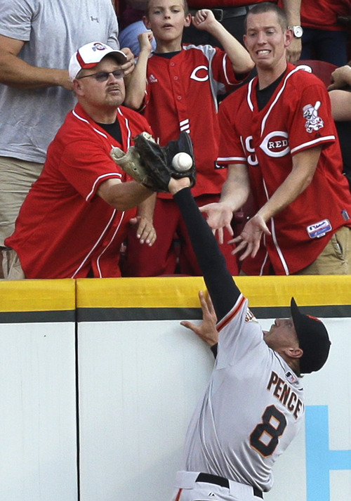 San Francisco Giants right fielder Hunter Pence (8) can't catch a ball hit by Cincinnati Reds' Shin-Soo Choo as a fan goes for the ball during the first inning of a baseball game, Tuesday, July 2, 2013, in Cincinnati. Umpires ruled the ball a ground rule double. (AP Photo/Al Behrman)
