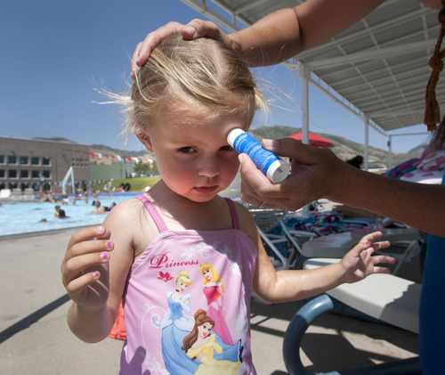 Steve Griffin   The Salt Lake Tribune   Haley Wall uses a sunscreen stick to apply protection to her two -year-old daughter, Elizabeth's, face during an outing at the Salt Lake CIty Sports Complex in Salt Lake City, Utah Tuesday July 2, 2013.