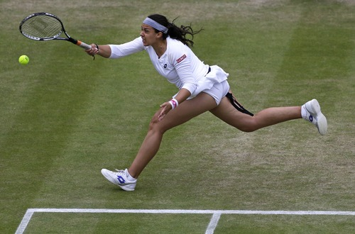 Marion Bartoli of France plays a return to Sloane Stephens of the United States in a Women's singles quarterfinal match at the All England Lawn Tennis Championships in Wimbledon, London, Tuesday, July 2, 2013. (AP Photo/Anja Niedringhaus)