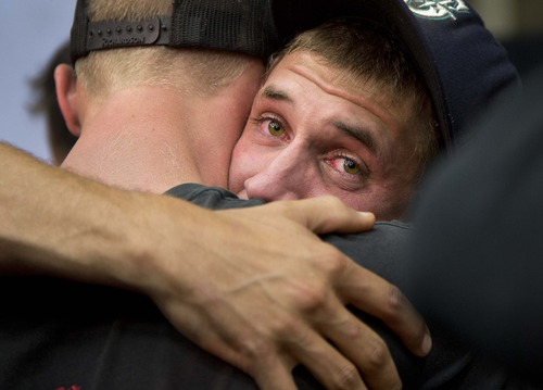 Prescott and other area department firefighters embrace during a memorial service, Monday, July 1, 2013 in Prescott, Ariz., The service was held for the 19 Granite Mountain Hotshot Crew firefighters who were killed Sunday, when an out-of-control blaze overtook the elite group. (AP Photo/Julie Jacobson)