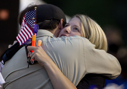 Mourners embrace before the start of a candlelight vigil in Prescott, Ariz. on Tuesday, July 2, 2013 to honor the 19 Granite Mountain Hotshot firefighters who were killed by an out-of-control blaze near Yarnell, Ariz. on Sunday. (AP Photo/Julie Jacobson)