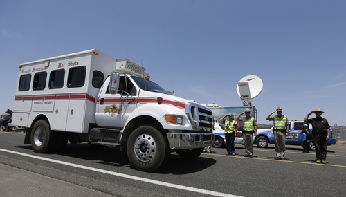 Chris Carlson  |  The Associated Press Officials salute and offer a moment of silence as a procession of the vehicles left by the 19 elite Hotshot crew members killed over the weekend are removed from the fire area near Yarnell, Ariz., Wednesday, July 3, 2013. Violent wind gusts on Sunday turned a small, lightning-ignited forest fire in the town into an out-of-control wildfire that left no escape for the team of Hotshots.