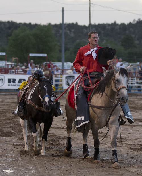 Julie Jacobson  |  The Associated Press A rodeo outrider leads a riderless horse with a firefighter's helmet and boots in the stirrups before the start of the Prescott Frontier Days Rodeo, Wednesday, July 3, 2013 in Prescott, Ariz. The notoriously rambunctious annual rodeo contest in Prescott added a solemn new ritual this week in tribute to the 19 firefighters who were killed Sunday near Yarnell, Ariz.