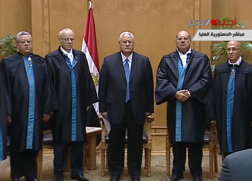 This image made from Egyptian State Television shows Egypt's interim president Adly Mansour, center, standing with judges during a swearing in ceremony in at the constitutional court in Cairo, Thursday, July 4, 2013. Egypt's chief justice of the Supreme Constitutional Court has been sworn in as interim president after Egyptians awoke Thursday to a new political reality after the military overthrew the country's first democratically elected president after only a year in office, shunting the Islamist leader aside in the same kind of Arab Spring uprising that brought him to power. (AP Photo/Egyptian State TV)