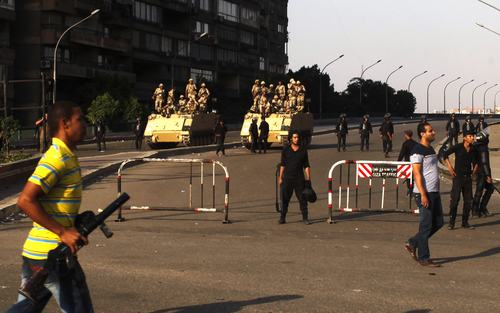 Army soldiers and policemen stand guard near supporters of overthrown President Mohamed Mursi and the Muslim Brotherhood, around Cairo University and Nahdet Misr Square in Giza, on the outskirts of Cairo July 4, 2013. The leader of the Muslim Brotherhood was arrested by Egyptian security forces on Thursday in a crackdown against the Islamist movement after the army ousted the country's first democratically elected president Mursi. At least 16 people have been killed and hundreds wounded in street clashes across Egypt since Mursi's overthrow. REUTERS/ Asmaa Waguih (EGYPT - Tags: POLITICS CIVIL UNREST MILITARY)
