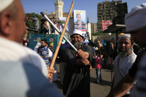 Supporters of Egypt's Islamist President Mohammed Morsi dance with sticks during a rally, in Nasser City, Cairo, Egypt, Thursday, July 4, 2013. The chief justice of Egypt's Supreme Constitutional Court was sworn in Thursday as the nation's interim president, taking over hours after the military ousted the Islamist President Mohammed Morsi. Adly Mansour took the oath of office at the Nile-side Constitutional Court in a ceremony broadcast live on state television. According to military decree, Mansour will serve as Egypt's interim leader until a new president is elected. A date for that vote has yet to be set. (AP Photo/Hassan Ammar)
