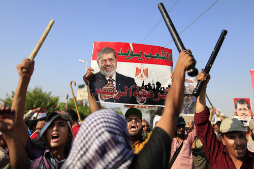 """Supporters of Egypt's Islamist President Mohammed Morsi chant slogans during a rally, in Nasser City, Cairo, Egypt, Thursday, July 4, 2013. The chief justice of Egypt's Supreme Constitutional Court was sworn in Thursday as the nation's interim president, taking over hours after the military ousted the Islamist President Mohammed Morsi. Adly Mansour took the oath of office at the Nile-side Constitutional Court in a ceremony broadcast live on state television. According to military decree, Mansour will serve as Egypt's interim leader until a new president is elected. A date for that vote has yet to be set. Arabic reads, """"the people support legitimacy for the president,"""".  (AP Photo/Hassan Ammar)"""