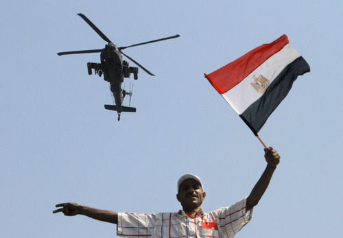 An military helicopter flies over an opponent if Egyptian Islamist President Mohammed Morsi as he waves a national flag, in Tahrir Square in Cairo, Egypt, Tuesday, July 2, 2013. With a military deadline for intervention ticking down, protesters seeking the ouster of Egypt's Islamist president sought Tuesday to push the embattled leader further toward the edge with another massive display of people power.(AP Photo/Amr Nabil)