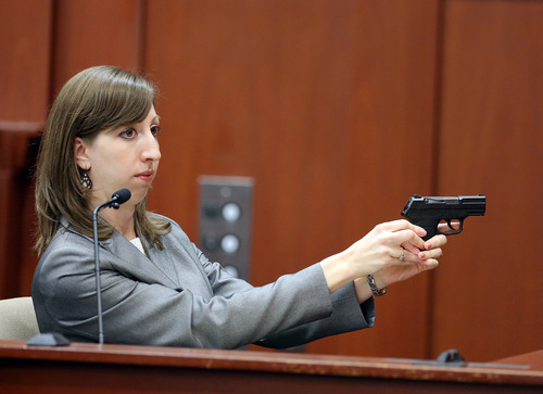 Amy Siewert, a firearms expert with the Florida Department of Law Enforcement, faces the jury as she demonstrates George Zimmerman's gun during his trial in Seminole circuit court, in Sanford, Fla., Wednesday, July 3, 2013. Zimmerman is charged with second-degree murder in the fatal shooting of Trayvon Martin, an unarmed teen, in 2012. (AP Photo/Orlando Sentinel, Jacob Langston, Pool)