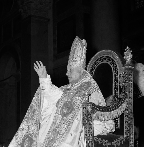FILE - In this Jan. 25, 1959 file photo, Pope John XXIII blesses spectators as he is carried on a portable throne to St. Paul's Basilica in Rome, outside the Vatican walls. Pope Francis on Friday, July 5, 2013 cleared Pope John Paul II for sainthood, setting up a remarkable dual canonization along with Pope John XXIII. (AP Photo)