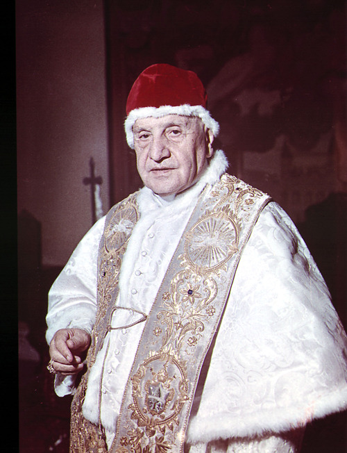 """FILE - In this file photo taken on April 15 1963, Pope John XXIII is wearing his """"Camauro"""", a red velvet cap, in his private library at the Vatican. Pope Francis has cleared John Paul II for sainthood, approving a miracle attributed to his intercession. Francis also decided Friday, July 5, 2013, to canonize another beloved pope, John XXIII, even though there has been no second miracle attributed to his intercession. The Vatican said Francis approved a decision by cardinals and bishops. The ceremonies are expected before the end of the year. (AP-Photo/Luigi Felici)"""