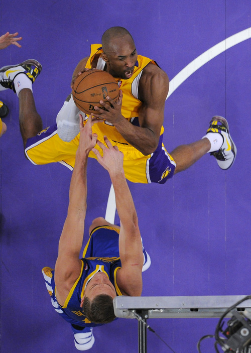 Golden State Warriors forward Andris Biedrins, below, of Latvia, blocks the shot of Los Angeles Lakers guard Kobe Bryant during the first half of their NBA basketball game, Friday, April 12, 2013, in Los Angeles. (AP Photo/Mark J. Terrill)
