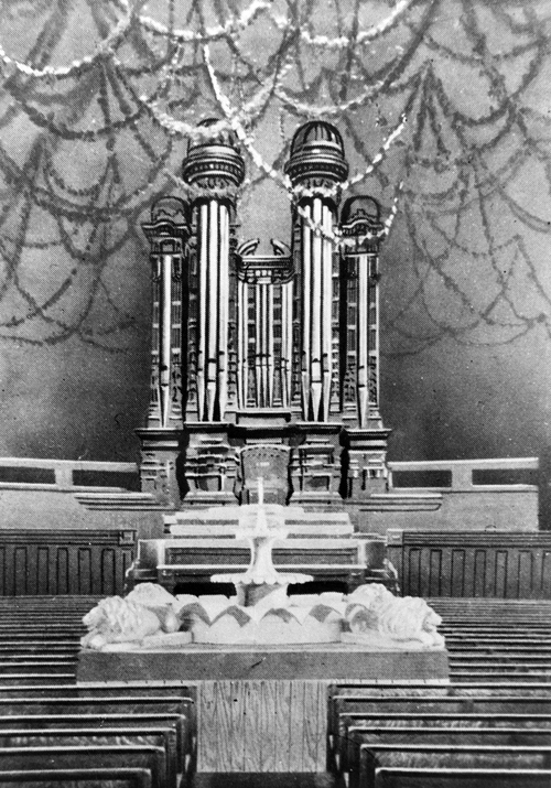 (Salt Lake Tribune archive)  Photograph of the fountain on the interior of the newly completed Salt Lake Tabernacle around 1870. The Tabernacle roof was constructed in an Ithiel Town lattice-truss arch system that is held together by dowels and wedges. The building has a sandstone foundation, and the dome is supported by 44 sandstone piers. The overall seating capacity of the building is 7,000, which includes the choir area and gallery (balcony).