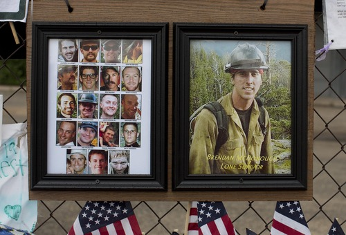 Photos of the 19 fallen Granite Mountain Hotshot firefighters and the lone survivor of the fatal blaze hang on the fence outside Fire Station No. 7, Friday, July 5, 2013 in Prescott, Ariz. Nearly a week after 19  Granite Mountain Hotshot firefighters died battling a blaze near Yarnell, Ariz., mourners continue to visit and grow the memorial. (AP Photo/Julie Jacobson)